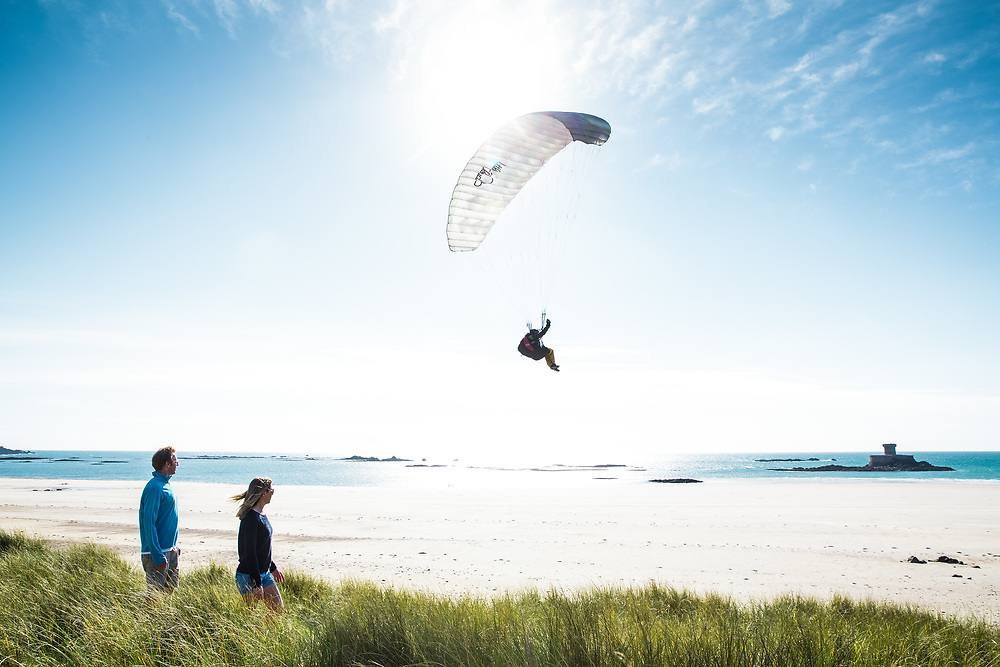 Couple walking through the sand dunes and watching a paraglider as they descend over St Ouen's Bay, Jersey with La Rocco Tower in the distance on a beautiful sunny day