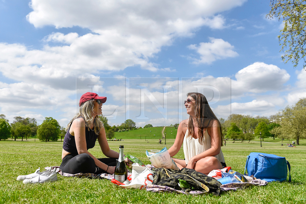 © Licensed to London News Pictures. 04/05/2018. LONDON, UK.  Londoners Christina Foster (L) and Alessandra Porto (R) enjoy a picnic in the sunshine and warm temperatures in Primrose Hill.  Forecasters predict that the upcoming Bank Holiday Monday could see temperatures exceed 25C.  Photo credit: Stephen Chung/LNP