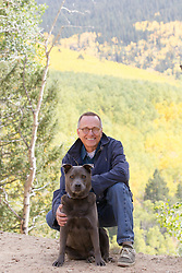 handsome sixty something year old man and a mixed breed dog in the Santa Fe Mountains during the changing of the leaves