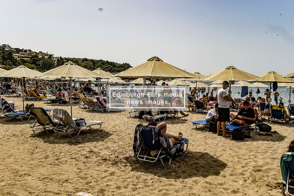 People sunbathe on sunbeds during the official reopening of organized beaches to the public in Athens on May 16, 2020. Hundreds of organized beaches opened to the public on 16 May, though they are to operate subject to strict health and safety guidelines due to the coronavirus pandemic, amid forecasts of a record heat wave<br /> <br /> Pictured: <br /> Dimitris Lampropoulos    EEm date