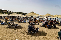 People sunbathe on sunbeds during the official reopening of organized beaches to the public in Athens on May 16, 2020. Hundreds of organized beaches opened to the public on 16 May, though they are to operate subject to strict health and safety guidelines due to the coronavirus pandemic, amid forecasts of a record heat wave<br /> <br /> Pictured: <br /> Dimitris Lampropoulos  | EEm date