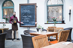 Young man pointing at chalkboard menu in restaurant