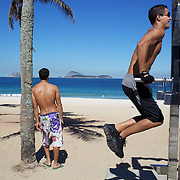A man works out at a fitness station on Ipanema beach, Rio de Janeiro,  Brazil. 6th July 2010. Photo Tim Clayton..