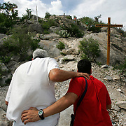 Alberto Salinas leans on Tony Medina while they climb past the crosses at Sierra de la Campana outside on Espinazo, Nuevo Leon, Mexico. Salinas' health problems have increased to where he has trouble working and may have to give up channeling and concentrate on his own wellness. <br /> Nathan Lambrecht/The Monitor