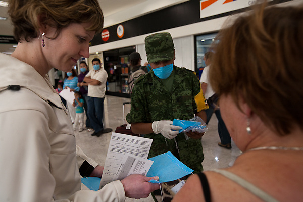 26 April 2009,  Mexico City, Mexico--- Mexican soilders greet tourists at the Mexico City airport with surgical masks and voluntary surveys about thier health. All transportation into and out of the country remains open.      --- Image by © Trevor Snapp