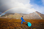 Lukasz Gryglicki rolls a fuel drum, pushed inland by high winds during a violent storm, back towards the shore at the Polish Polar Station in Hornsund, Svalbard.