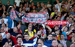 Arsenal fans in the stands hold up banners and scarves honouring outgoing manager Arsene Wenger