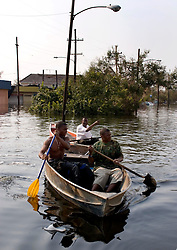 05 Sept  2005. New Orleans, Louisiana. Post hurricane Katrina.<br /> Aaron Smith and his father John Smith (mid) and his sons Aaron (l) and Jonas (rt)try to work out their directions on the flooded roads in Uptown New Orleans as the family attempt to rescue their business.<br /> Photo; ©Charlie Varley/varleypix.com