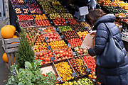 A shopper chooses fruits at local grocer 'Bora & Sons', a fruit and veg retailer which displays its produce outside its high street business on Lordship Lane in East Dulwich, on 25th October 2021, in London, England.