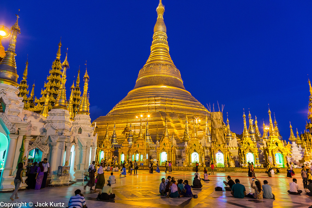 15 JUNE 2013 - YANGON, MYANMAR: Shwedagon Pagoda in the evening. The Shwedagon Pagoda is officially known as Shwedagon Zedi Daw and is also called the Great Dagon Pagoda or the Golden Pagoda. It is a 99 metres (325ft) tall pagoda and stupa located in Yangon, Burma. The pagoda lies to the west of on Singuttara Hill, and dominates the skyline of the city. It is the most sacred Buddhist pagoda in Myanmar and contains relics of the past four Buddhas enshrined: the staff of Kakusandha, the water filter of Koṇāgamana, a piece of the robe of Kassapa and eight strands of hair fromGautama, the historical Buddha. The pagoda was built between the 6th and 10th centuries by the Mon people, who used to dominate the area around what is now Yangon (Rangoon). The pagoda has been renovated numerous times through the centuries. Millions of Burmese and tens of thousands of tourists visit the pagoda every year, which is the most visited site in Yangon.    PHOTO BY JACK KURTZ