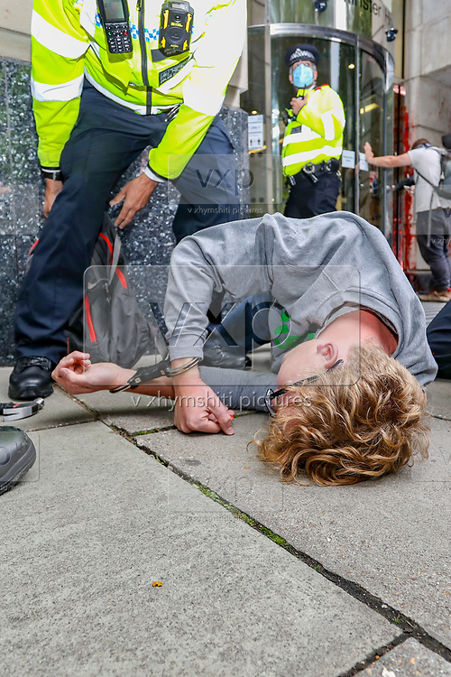 Police look after a member of Extinction Rebellion activists group who appears to have been hurt during a rapid intervention of the officer in picture meanwhile the activist in picture tried to spray a political message outside Department for Transport building in Horseferry Road in central London on Friday, Sept 4, 2020. There are other Extinction Rebellion protests ongoing in London. Police closed Horseferry Road both ways as a group of protestors from Parliament Square marched towards Department for Transport demanding an end of HS2 construction. Environmental nonviolent activists group Extinction Rebellion enters its 4th day of continuous ten days protests to disrupt political institutions throughout peaceful actions swarming central London into a standoff, demanding that central government obeys and delivers Climate Emergency bill. (VXP Photo/ Vudi Xhymshiti)