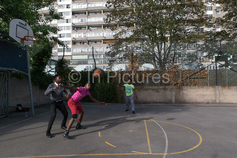 Teenagers play basketball at the Aylesbury Estate, a large housing estate located in Walworth, on 24th June 2016 in South London, United Kingdom. The Aylesbury Estate contains 2,704 dwellings and was built between 1963 and 1977. The estate is partially occupied and is currently undergoing a major redevelopment.
