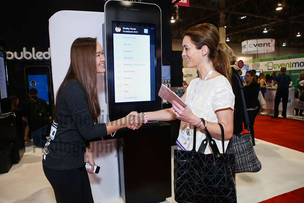 A conference attendee makes connections at the DoubleDutch booth at IMEX America.
