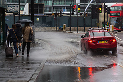 Constant rain on Bank Holiday Sunday leaves large puddles at Old Street Roundabout, with this red BMW splashing water onto the pavement, drenching pedestrians. London, August 26 2018.