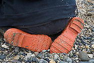bottom of rubber boats and rear of peerson on a rocky ocean beach