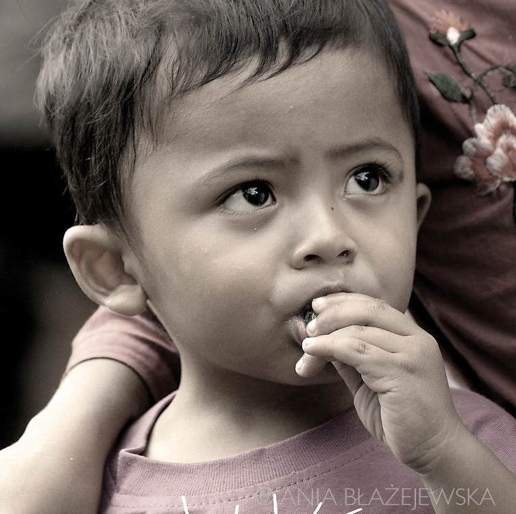Indonesia, Bali. Portrait of a little boy from Ubud eating a candy.