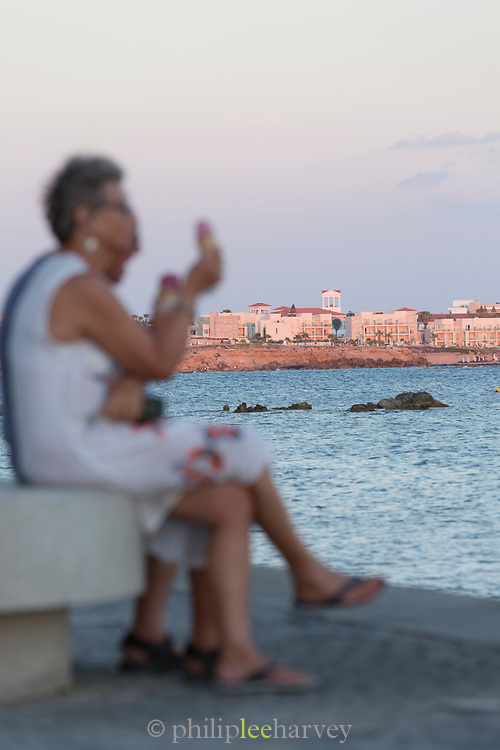 Couple eating ice cream on bench with coastal town in background, Paphos, Cyprus