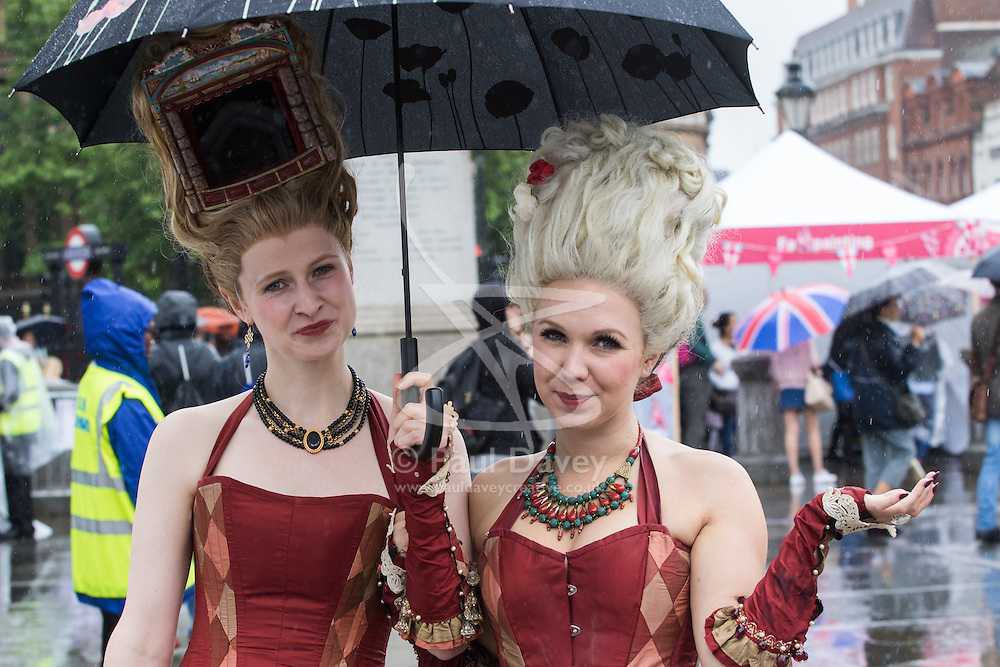 Trafalgar Square, London, June 12th 2016. Rain greets Londoners and visitors to the capital's Trafalgar Square as the Mayor hosts a Patron's Lunch in celebration of The Queen's 90th birthday. PICTURED: Two women in costume pose for the camera.
