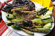 Grilled vegetables: green bell peppers, zucchini courgette squash, aubergine eggplant, Tradita traditional restaurant, Shkodra. Albania, Balkan, Europe.
