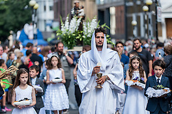 © Licensed to London News Pictures. 19/07/2015. London, UK. The procession of Our Lady of Mount Carmel, held on the Sunday after 16 July – is Little Italy's most important event.  Taking place around St Peter church in Clerkenwell, the oldest Italian church in London, it is believed that the procession was the first outdoor Roman Catholic religious event held in England since the Reformation in the sixteenth century; and has been running annually since the 1880s, apart from the two World Wars.  The procession includes musicians, icons, religious statues and floats with tableaux showing Biblical scenes as well as nearby stalls selling Italian food. Photo credit : Stephen Chung/LNP