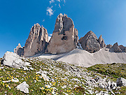 """Hike for spectacular views around Tre Cime di Lavaredo (Italian for """"Three Peaks of Lavaredo,"""" also called Drei Zinnen or """"Three Merlons"""" in German), which are distinctive icons of the Alps, in the Sexten Dolomites of northeastern Italy, Europe. Until 1919 the peaks formed part of the border between Italy and Austria. Now they lie on the border between the Italian provinces of South Tyrol and Belluno and still are a part of the linguistic boundary between German-speaking and Italian-speaking majorities. Cima Grande rises to 2999 meters (9839 feet), between Cima Piccola  2857 m (9373 ft) and Cima Ovest  or """"Western Peak"""" 2973 m (9754 ft). The Dolomites were declared a natural World Heritage Site (2009) by UNESCO. Panorama stitched from 4 overlapping photos."""