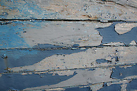 Peeling blue paint on the side of a rowing boat