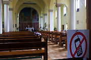 No mobile phones sign and interior of the 1930s built St. Lawrence's Catholic church in Feltham, London.