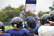 Head coach Joseph Gillespie calls the play for the offense at Stephenville High School in Stephenville, Texas on November 5, 2013. (Cooper Neill / for The New York Times)