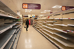 © Licensed to London News Pictures. 20/03/2020. London, UK. A shopper looks at empty shelves in the pasta and rice aisle of a Sainsbury's supermarket in New Cross, south London. Certain food products continue to be in high demand as the Coronavirus outbreak continues to escalate. Photo credit: Rob Pinney/LNP