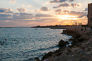 People swim in the Mediterranean Sea as the sun sets behind ancient columns at Al-Mina Archaeological Site in Tyre, Lebanon.
