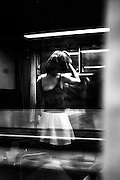 June 2015. Brussels. A young girl looks her reflect on the train's window while we're arriving at Central station.
