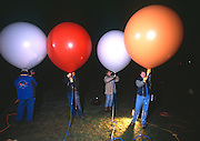 John Ninomiya, a cluster balloonist gets help from voluteers filling a bouquet of 4ft in diameter and 7ft in diameter balloons.