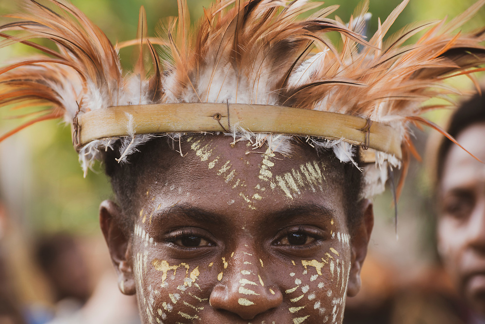 Close-up of the face of a young woman wearing a feather hat during a celebration at Yar village in the East Sepik Province of Papua New Guinea. The community was celebrating the dedication of the New Testament in the Waran language, one of the hundreds of languages in the country.<br /> <br /> (June 21, 2019)