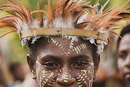 Close-up of the face of a young woman wearing a feather hat during a celebration at Yar village in the East Sepik Province of Papua New Guinea. The community was celebrating the dedication of the New Testament in the Waran langauge, one of the hundreds of languages in the country. (June 21, 2019)