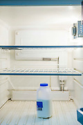 An almost empty fridge containing only a half empty pint of milk in Hackney, London, United Kingdom. It reflects the increasing number of people who are unable to afford food and live below the poverty line in the UK. Every day people in the UK go hungry for reasons ranging from redundancy to receiving an unexpected bill on a low income.
