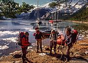 Trekkers leave beach for peak in Darwin Range, yachts anchored in Seno ( fjord) Pia, Isla Grande, Tierra del Fuego, Chile.