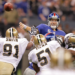 2009 October 18: New York Giants quarterback Eli Manning (10) throws under pressure from the New Orleans Saints defense during a 48-27 win by the New Orleans Saints over the New York Giants at the Louisiana Superdome in New Orleans, Louisiana.
