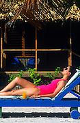 Woman sunbathing by a beach bungalow, Belize
