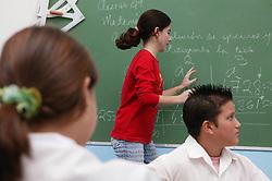 White woman teacher writing on blackboard in classroom at Carlos J Finlay secondary school; Havana; Cuba,