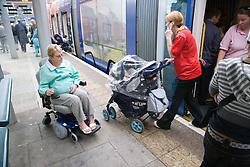 Woman wheelchair user approaching the tram,
