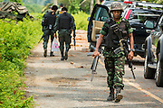 08 JULY 2013 - MAYO, PATTANI, THAILAND: A Thai soldier, carrying the rifle of one of his colleagues wounded in an IED blast, walks back to his vehicle after clearing the scene in Pattani province Monday. Eight Thai soldiers were injured - one seriouly and seven with minor injuries - when their truck was hit by an IED outside Mayo, Pattani province in southern Thailand Monday. The soldiers were returning from a teacher protection mission when their truck ran over the explosive. The attack was thought to be conducted by Muslim insurgents who have been battling the Thai government for greater autonomy. The conflict in southern Thailand has claimed about 5,000 lives since 2004.    PHOTO BY JACK KURTZ