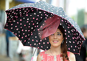 © Licensed to London News Pictures. 21/06/2012. Ascot, UK Woen with umbrellas. Ladies Day at Royal Ascot 21st June 2012. Royal Ascot has established itself as a national institution and the centrepiece of the British social calendar as well as being a stage for the best racehorses in the world.. Photo credit : Stephen Simpson/LNP