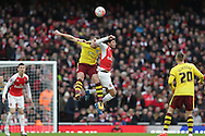 Sam Vokes of Burnley challenges Mohamed Elneny of Arsenal in the air.The Emirates FA cup, 4th round match, Arsenal v Burnley at the Emirates Stadium in London on Saturday 30th January 2016.<br /> pic by John Patrick Fletcher, Andrew Orchard sports photography.