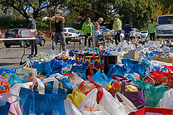 JOHANNESBURG, SOUTH AFRICA - APRIL 23: Volunteers operate a drive through food donation drive. Pirates Sports Club co-ordinated the public donations of approxiamately 1000 bags of food and goods, to be distributed to people in need, through various aid efforts on April 23, 2020 in Johannesburg South Africa. Under pressure from a global pandemic. President Ramaphosa declared a 21 day national lockdown extended by another two weeks, mobilising goverment structures accross the nation to combat the rapidly spreading COVID-19 virus - the lockdown requires businesses to close and the public to stay at home during this period, unless part of approved essential services. (Photo by Dino Lloyd)