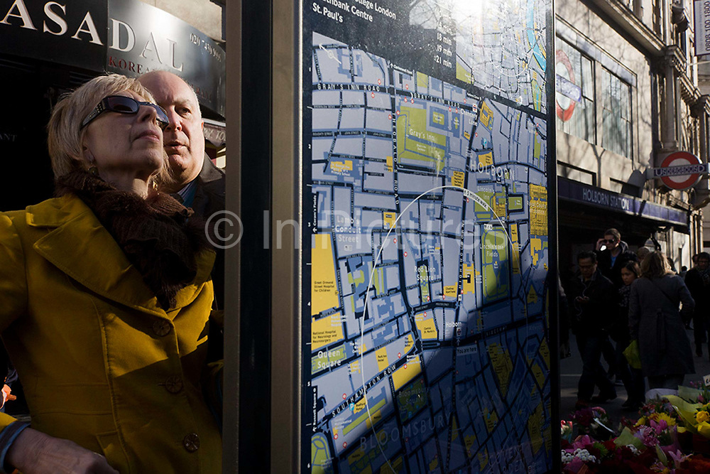 Tourists examine one of the many street maps of central London, this one located outside Holborn station.