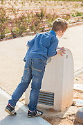 young, red haired boy drinks water from a drinking fountain