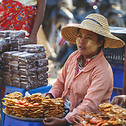 Lady selling shrimp patties on the banks of the Ayerawady River, Old Bagan. Along with the shrimp and the rice flour batter they often have onion and beansprouts added to give an extra texture ...and the shells on for extra crunch.