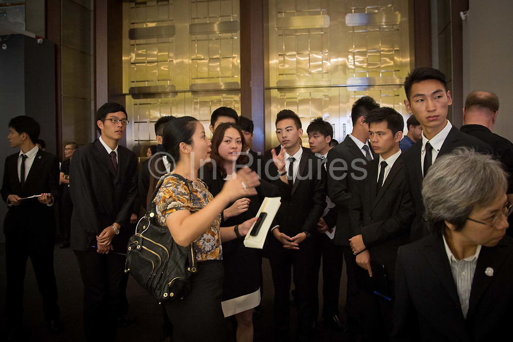 """Ushers gets a briefing just prior to Christie's very first mainland China auction in Shanghai, China September 27,  2013. Both Southeby's and Christie's have opened an office in Mainland China in the past year, however they face overwhelming odds as China's state-owned auction houses such as Poly and Jiamu enjoys a near monopoly over China's art procurement market as foreigners are not allowed to buy vaguely defined """"historical"""" art."""