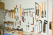Carpenter's workshop tools hang on a wall