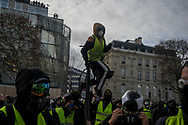 A protester climbing on a red light on the Champs Elysee. More than 125000 gathered in Paris for the Gilets Jaune (Yellow vest) protest. Soon the protest turned violent an protesters clashed with the police, tear gas and flash bombs were fired, many injured and arrested by the police. Paris December 6th 2018. Federico Scoppa
